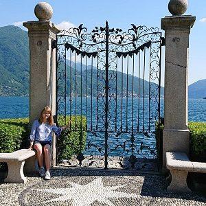 ein Mädchen posiert vor einem Tor an einem See