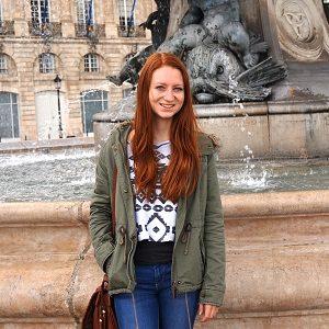 Ein Mädchen steht vor einem Brunnen
