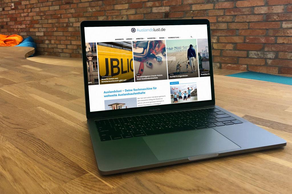 Laptop auf Holztisch mit Website auslandslust.de geöffnet