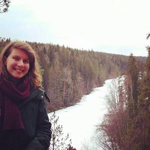 Ein Mädchen posiert vor einem Wald an einem Fluss