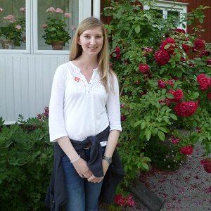 Ein Mädchen vor einer Hecke mit Blumen