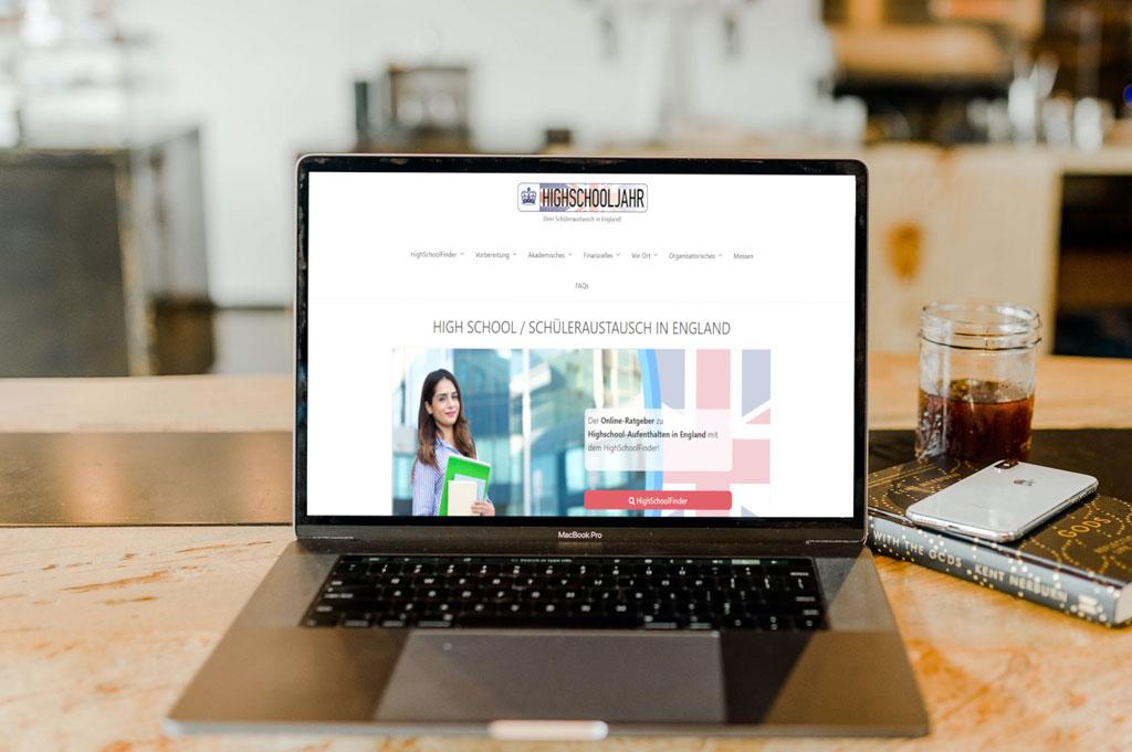 Laptop neben Buch und Smartphone auf Tisch mit Website highschooljahr-england.de geöffnet