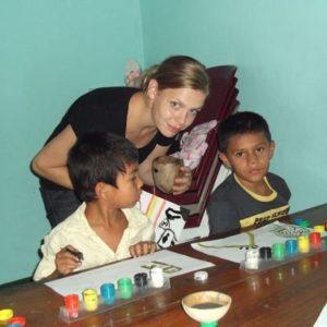 Frau betreut Jungen beim Malen