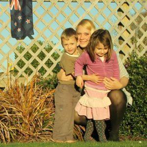 Frau umarmt Kinder im Garten vor neuseeländischer Flagge