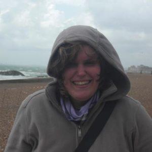 Lachende Frau mit Kaputze im Wind