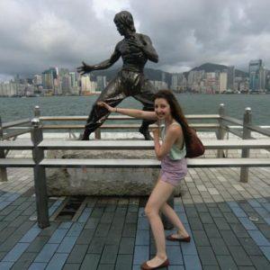 Jugendliche am Posen mit der Kampfsport-Statue in China