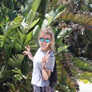 Junge Frau vor Palmen
