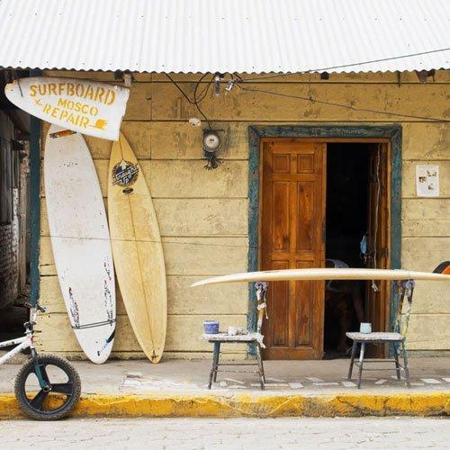 weltweiser · Auf zwei Stühlen gelegtes Surfboard auf Geshsteig vor einer Surfboard-Werkstatt