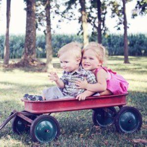 Kleinkinder sitzen in einem roten Wagen