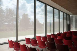 Rote Stuhlreihen in gläsernem Konferenzsaal