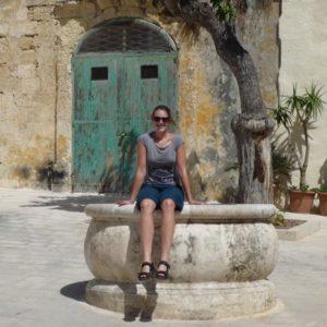 Frau sitzt lächelnd vor einer Häuserfront