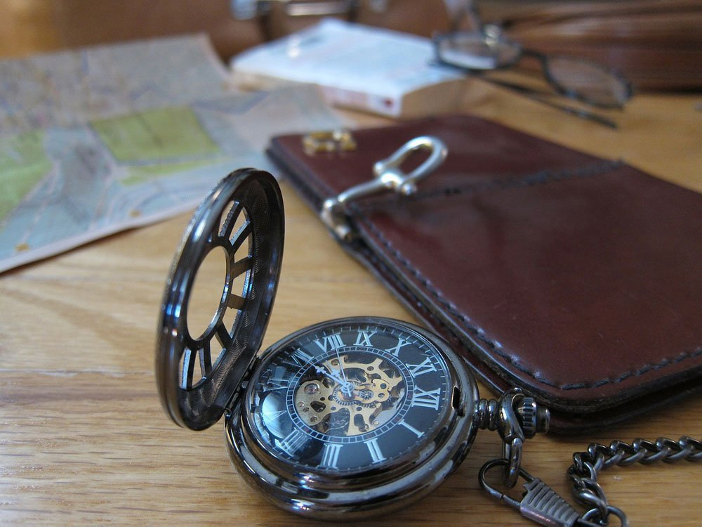 Alte Taschenuhr mit Karte und Buch im Hintergrund