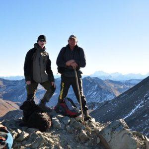Ein Jungendlicher und ein Mann mit einem Hund am Wandern in den Bergen Neuseelands