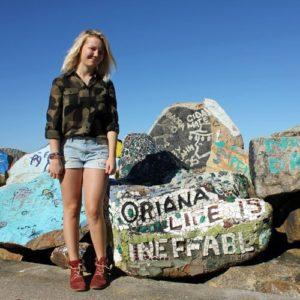 Mädchen neben Felsen mit Mosaik