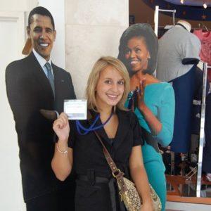 Junge Frau vor Pappfiguren von Michelle und Barack Obama