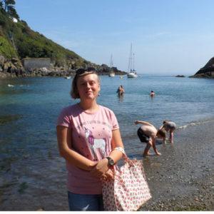 Ein Mädchen in einer Bucht an der Küste Cornwalls