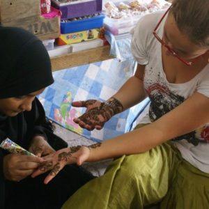 Ein Mädchen bekommt Henna-Tattoos auf ihre Hände gemalt