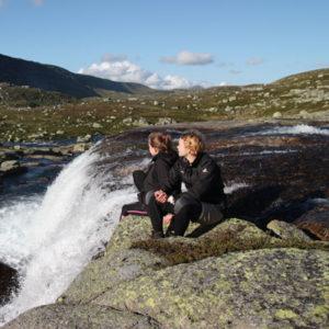 Zwei Jugendliche an einem Wasserfall in Skandinavien
