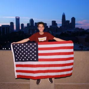 Jugendlicher vor einer Skyline mit USA-Flagge in der Hand