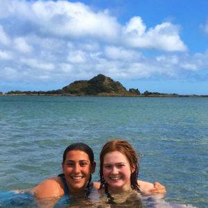 Zwei Jugendliche im Meer vor einer Insel