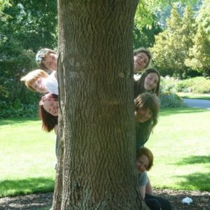 Kinder hinter einem Baum