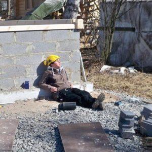 Ein Junge lehnt in der Sonne an einer Steinmauer auf einer Baustelle
