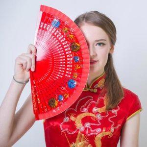 Schülerin in traditioneller chinesischer Kleidung mit einem Fächer