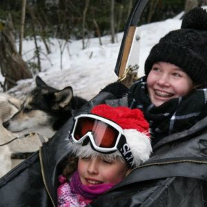 Zwei Mädchen im Hundeschlitten mit Huskeys