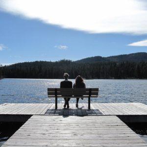 Jugendliche auf einer Bank auf einem Steg am See
