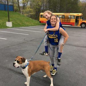 Zwei Jugendliche mit Hund vor einem Schulbus