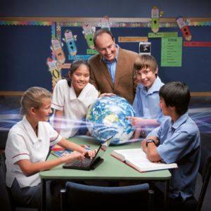 Vier Schüler mit einem Lehrer und einer Weltkugel