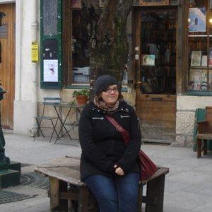 Studentin in Frankreich vor einer alten Buchhandlung