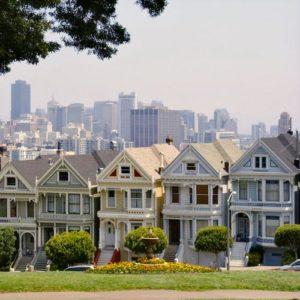 Einfamilienhäuser in Reihe vor dem Hintergrund einer Skyline
