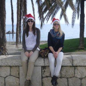 Zwei junge Frauen auf einer Mauer vor einem Strand