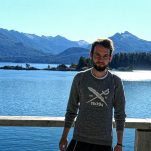 Jugendlicher vor einem See mit Bergen