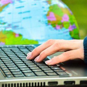 Notebook-Tastatur mit Globus im Hintergrund