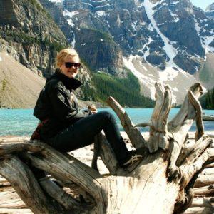 Ein Mädchen vor einem See mit schneebedeckten Bergen im Hintergrund