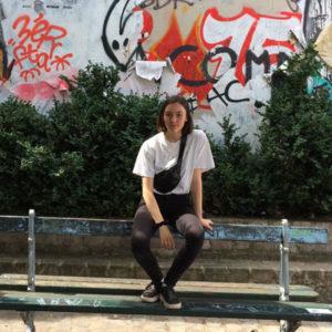 Jugendliche auf einer Bank vor einer Wand mit Graffitis